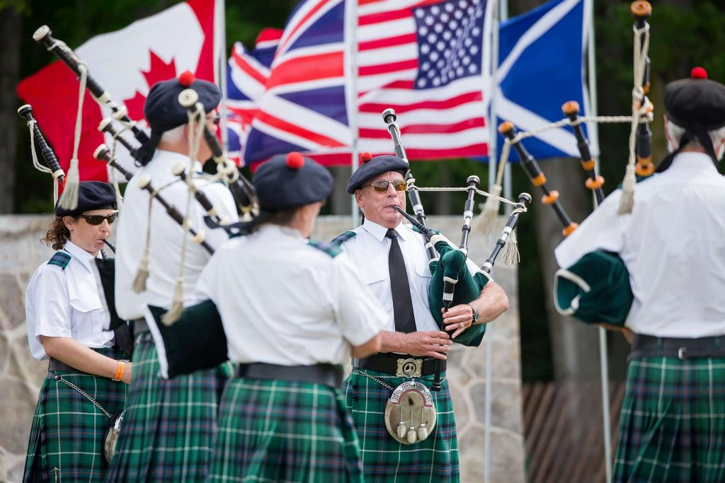 Playing bagpipes with flags in background.